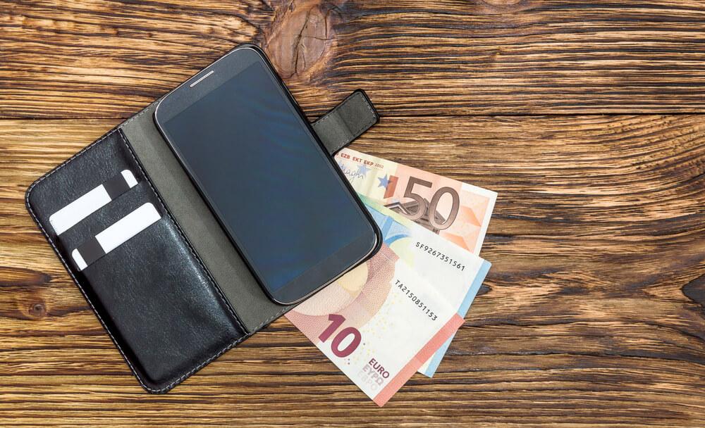 Geldscheine liegen unter einem Smartphone.