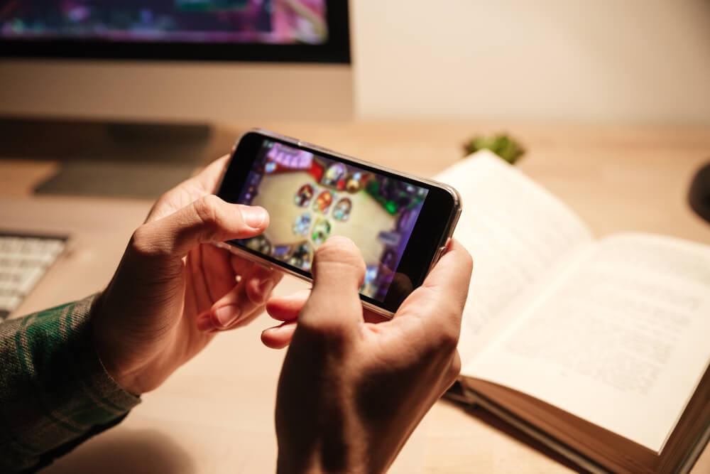 Mann spielt auf einem Smartphone ein Spiel.